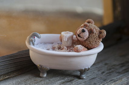 Teddy bear taking bath with a cup of beer