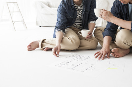 Couple drinking coffee while watching the floor plan